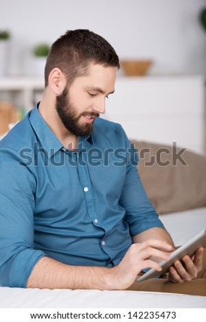 Portrait of happy young man holding digital tablet while sitting on sofa - stock photo