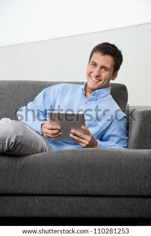 Portrait of happy young man in formal wear holding digital tablet while sitting on sofa - stock photo