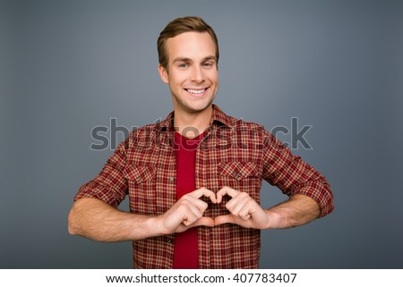 Portrait of happy young man making heart with fingers - stock photo