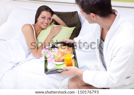 Portrait of happy young man serving breakfast for his girlfriend in bed at home - stock photo