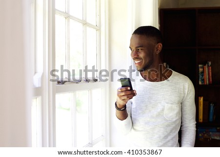 Portrait of happy young man standing by a window at home with a mobile phone  - stock photo