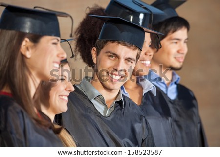 Portrait of happy young man standing with students on graduation day in college - stock photo