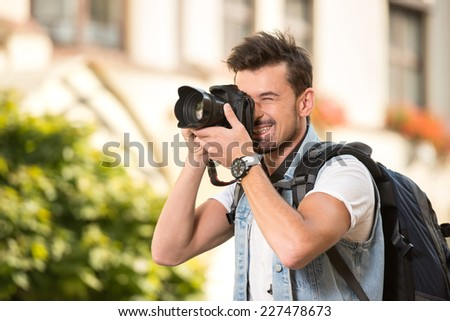 Portrait of happy young man, tourists with camera in the city. - stock photo