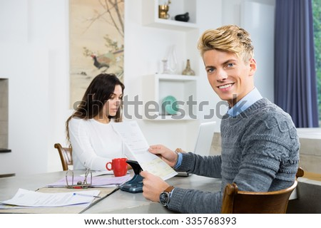 Portrait of happy young man with woman calculating personal finance at home - stock photo