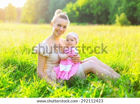 Portrait of happy young mother and baby little daughter wearing a dress together sitting on the grass meadow in sunny summer day, evening sunset sunlight - stock photo