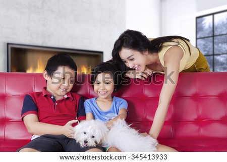 Portrait of happy young mother and her children playing their puppy on the sofa at home - stock photo