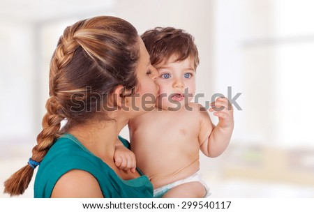 Portrait of happy young mother holding on hands cute little son and kissing him with love, with pleasure spending time at home, enjoying motherhood - stock photo