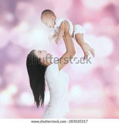 Portrait of happy young mother playing with her baby and throw up the baby, shot with a bokeh background - stock photo