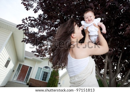 Portrait of happy young mother with baby girl outdoors - stock photo