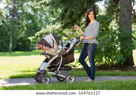 Portrait of happy young mother with cell phone and baby carriage walking in park - stock photo