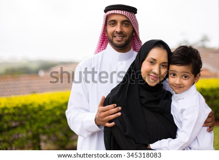 portrait of happy young muslim family outdoors - stock photo