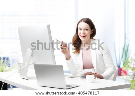 Portrait of happy young office worker sitting in front of computer at her workstation in an office and working on new presentation. - stock photo