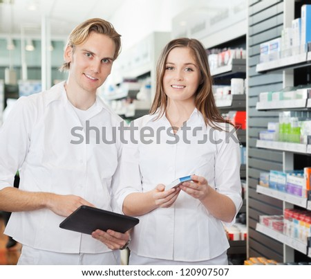 Portrait of happy young pharmacists with digital tablet in pharmacy - stock photo