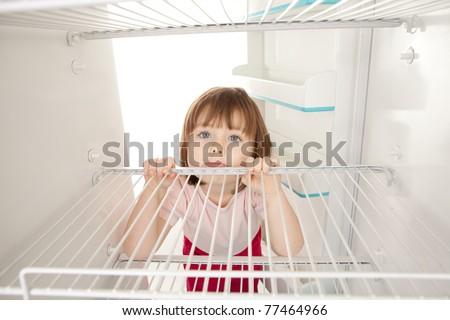 Portrait of happy young preschool girl looking in empty refrigerator. - stock photo