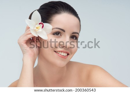 Portrait of happy young pretty woman, holding one nice orchid on the head as the hair accessory. Isolated on the white background - stock photo