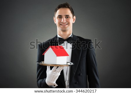 Portrait of happy young waiter holding house model in tray against gray background - stock photo