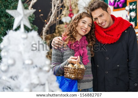 Portrait of happy young woman carrying bauble basket while standing with man in Christmas store - stock photo