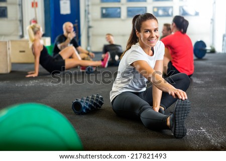 Portrait of happy young woman doing stretching exercise at cross training box - stock photo