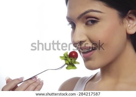 Portrait of happy young woman eating salad isolated over white background - stock photo