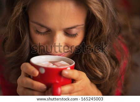 Portrait of happy young woman enjoying cup of hot chocolate with marshmallow - stock photo
