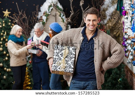Portrait of happy young woman holding Christmas present with family standing in background at store - stock photo