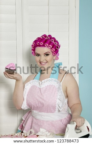 Portrait of happy young woman holding cupcake while ironing - stock photo
