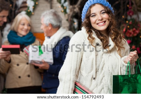 Portrait of happy young woman holding in sweater with family standing in background at Christmas store - stock photo