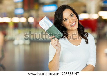 portrait of happy young woman holding passport and boarding pass at airport - stock photo