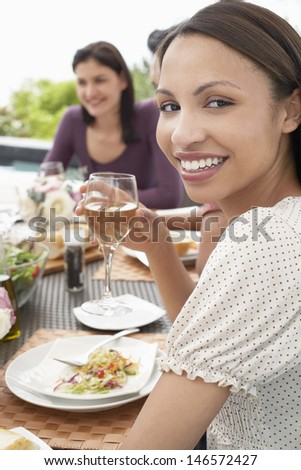 Portrait of happy young woman holding wineglass at dinner party - stock photo