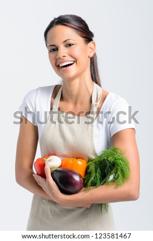 Portrait of happy young woman in apron holding fresh organic vegetables in her hands on grey background, promoting healthy diet and lifestyle - stock photo