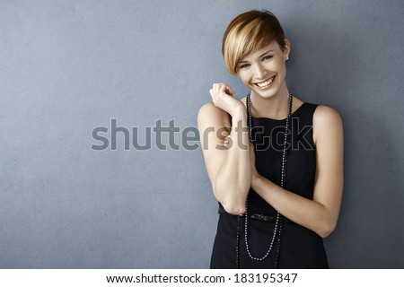 Portrait of happy young woman in black dress and pearls on grey background - stock photo