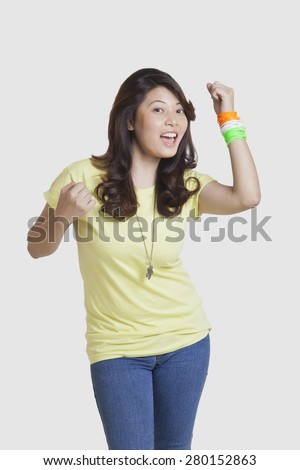 Portrait of happy young woman in casuals wearing Indian tricolor bangles over white background - stock photo