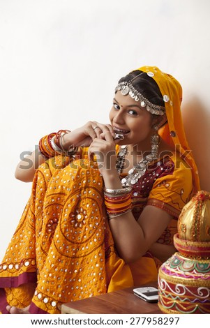 Portrait of happy young woman in chaniya choli eating chocolate against white background - stock photo