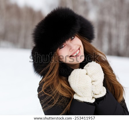 Portrait of happy young woman in luxury fur hat in winter - stock photo