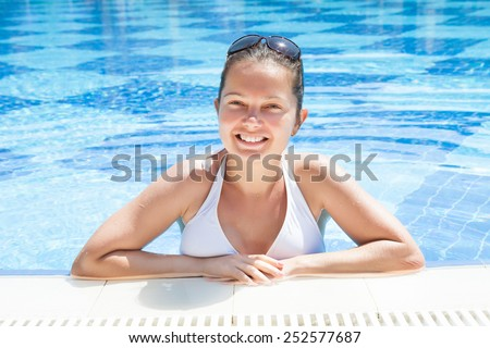 Portrait of happy young woman in pool at resort - stock photo