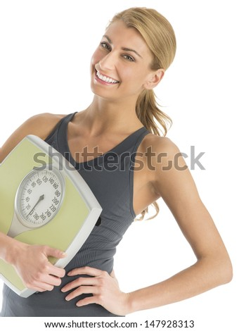 Portrait of happy young woman in sports clothing holding weight scale isolated over white background - stock photo