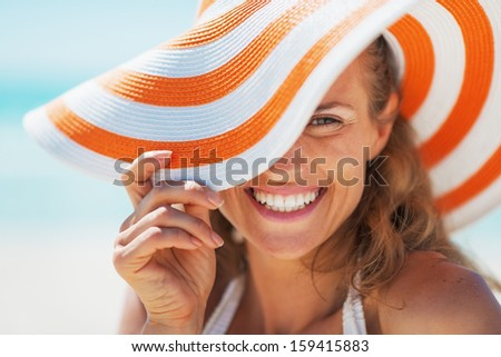 Portrait of happy young woman in swimsuit and beach hat - stock photo