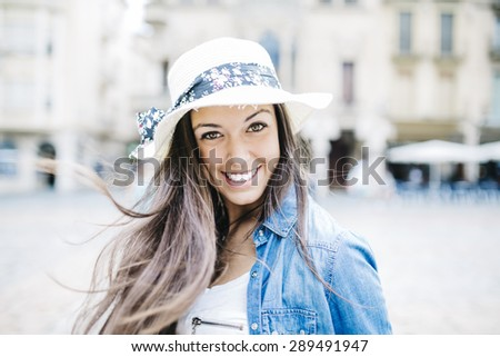 Portrait of happy young woman in urban background wearing casual clothes - stock photo