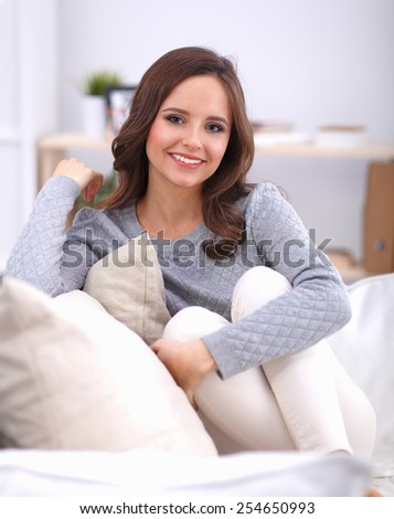 Portrait of happy young woman sitting on sofa - stock photo
