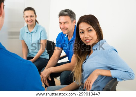 Portrait Of Happy Young Woman Sitting With Her Friends - stock photo