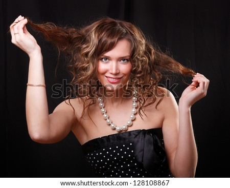 Portrait of happy young woman smiling and holding her hair, naked shoulders - stock photo