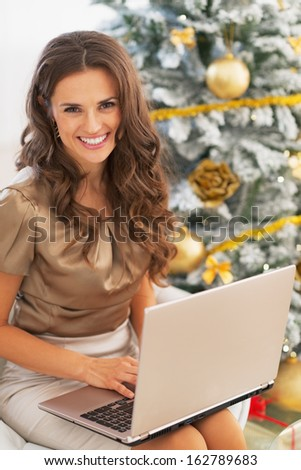 Portrait of happy young woman using laptop near christmas tree - stock photo