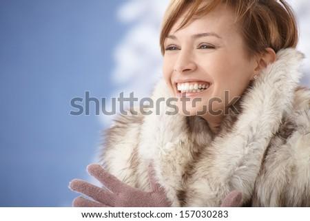 Portrait of happy young woman wearing fur coat, enjoying winter sunshine. - stock photo