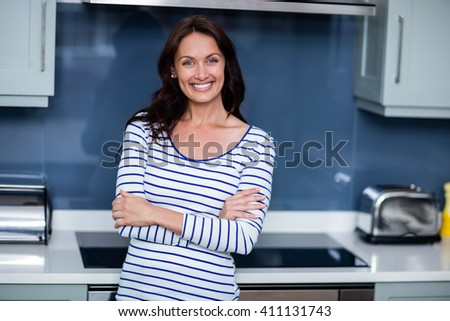 Portrait of happy young woman with arms crossed while standing in kitchen - stock photo