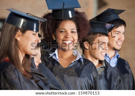 Portrait of happy young woman with friends in a row on graduation day at college - stock photo