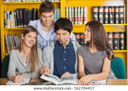 Portrait of happy young woman with friends studying in university library - stock photo