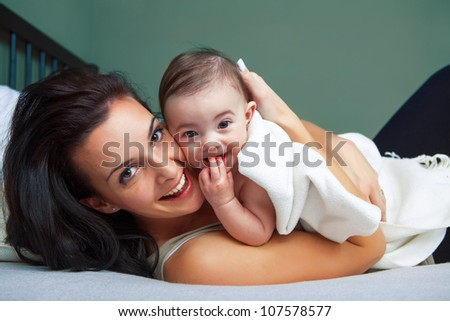 Portrait of happy young woman with her baby - stock photo