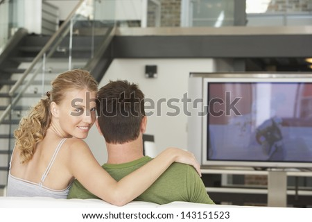Portrait of happy young woman with man watching TV at home - stock photo