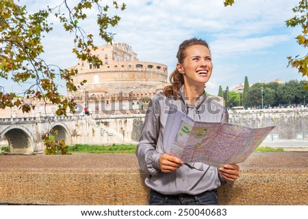 Portrait of happy young woman with map examining attractions on embankment near castel sant'angelo in rome italy - stock photo