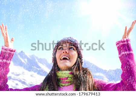 Portrait of happy young woman with open arms under snowflakes in mountains. - stock photo